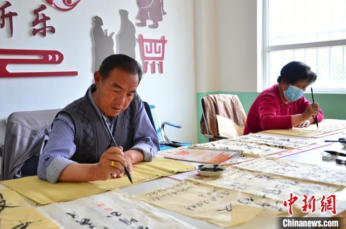 图为退休职工在华隆路社区内练习书法。 鲁丹阳 摄