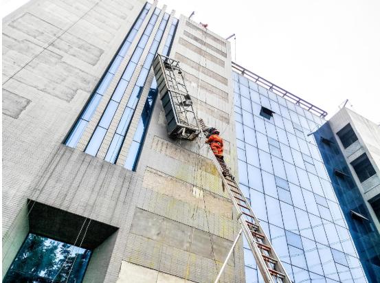 武汉一科技园内两名施工人员被困外墙吊篮很危险